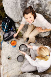 Girls cooking camping. Two friendly women cook up some food while camping in the wilderness. outdoor hiking lifestyle concept royalty free stock images