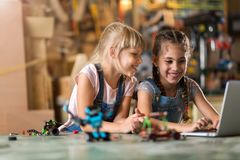 Girls cooperating while making a robot Royalty Free Stock Image