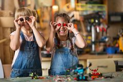 Girls cooperating while making a robot. Small girls cooperating while making a robot royalty free stock images