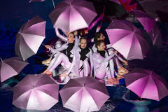Girls in costume with umbrellas performing in pool. MOSCOW - DEC 21: Girls in costume with umbrellas performing in pool at Show Olympic champions in synchronized royalty free stock photos