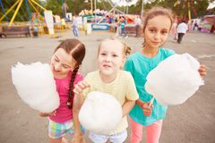 Girls with cotton candy. Cute girls eating cotton candy outdoors Royalty Free Stock Image