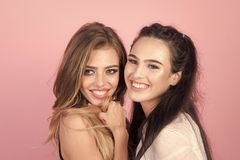 Girls couple, love relations, friendship. Women with blonde, brunette hair on pink background. women with long hair, lesbian. happy friends, family royalty free stock photography