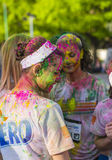 Girls covered in colored powder. Side profile of teenage girl painted with colored powder and surrounded by other participants at the Color Run event on April 26 Stock Image