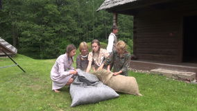 Girls cram hay bags Stock Images