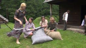 Girls cram hay bags stock footage