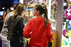 Girls in the crane machine. 3 girls are playing in a crane machine in Houston, Texas Royalty Free Stock Photography