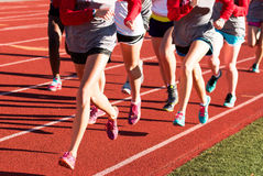 Girls cross country team doing intervals together. Girls cross country workout running intervals together on a red track while wearing spikes Royalty Free Stock Images