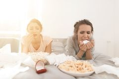 Girls are crying at the hen-party. They are lying on the bed and an engagement ring is near them. The girls are crying at the hen-party. They are lying on the stock image