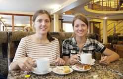 Girls with a cup of tea at coffee-room. Beautiful girls relaxing at coffee-room with a cup of tea royalty free stock images