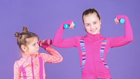 Girls cute kid exercising with dumbbells. Motivation and sport example concept. Toddler repeat exercise after sister. Sport exercises for kids. Healthy stock photos