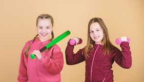 Girls cute kids with sport equipment dumbbells and baseball bat. We love sport. Child might excel in completely. Different sport. Friends ready for training royalty free stock photography