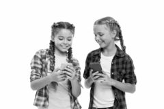 Girls cute small children smiling to phone screen. They like internet surfing social networks. Problem of young. Generation. Mobile phone and internet addiction stock photo