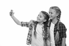Girls cute small children smiling to phone screen. They like taking selfie for social networks. Problem of young. Generation. Mobile phone dependence. Mobile stock image