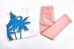 Girls cute summer cotton attire. White printed t-shirt and peach color trousers for young girl on white background Stock Photos