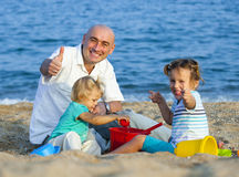 Girls with dad playing at sea Royalty Free Stock Photography