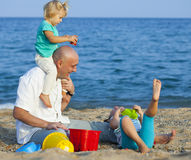 Girls with dad playing at sea Royalty Free Stock Image