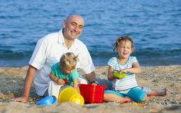Girls with dad playing on  sea shore Royalty Free Stock Photography