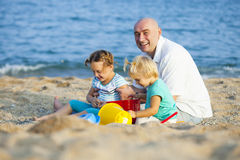 Girls with dad playing on  sea shore Royalty Free Stock Photos