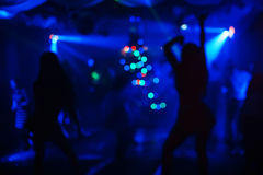 Girls dance in night club on stage a few blurred silhouettes. With blurred blue background and lights Stock Photo