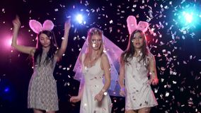 Girls dancing at bachelorette party against stroboscope lamps glitter confetti. Girls dancing at bachelorette party making blowing kisses against stroboscope stock video footage