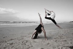 Girls dancing on beach. Two athletic girls vigorously dancing and leaping on a sandy beach. Color desaturated
