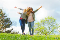 Girls dancing in the park. Young carefree women dancing on a meadow Royalty Free Stock Images