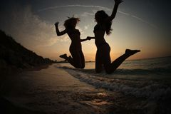 Girls DANCING IN SUNSET ON SEA Royalty Free Stock Photos