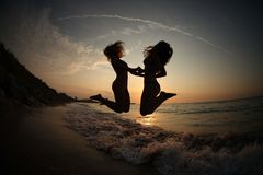 Girls DANCING IN SUNSET ON SEA Stock Photography