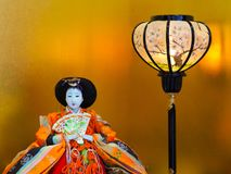 Japanese girls day empress doll. Girls day, called Hinamatsuri, doll display in Japan. Vibrant, colorful Empress doll with lantern in front of golden background royalty free stock images