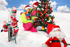 Girls decking up the Christmas tree. Two girls in Santa Claus cap decking up the Christmas tree at snow Stock Images