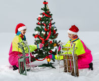 Girls decking up the Christmas tree. Two girls in Santa Claus cap decking up the Christmas tree at snow Stock Photo