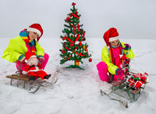 Girls decking up the Christmas tree. Two girls in Santa Claus cap decking up the Christmas tree at snow Royalty Free Stock Photo