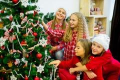 Girls decorate the Christmas tree Stock Photos