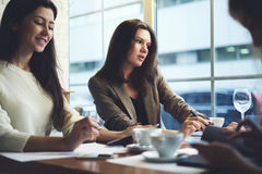Girls designers clothes working together enjoying coffee and conversation before event begins sharing work experience. Group of young skilled talented female royalty free stock image