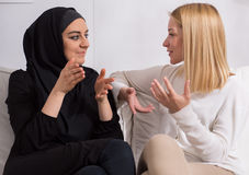 Girls of different ethnicity. Two beautiful girls of different ethnicity talking Stock Photo