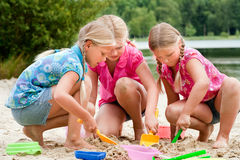 The girls digging in the sand Royalty Free Stock Photo