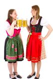 Girls in dirndl clinking their glasses Royalty Free Stock Images
