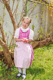 Girls in the dirndl sit in the garden and plays laughing with Easter eggs Stock Photo