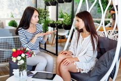 Girls discuss business cafe portrait two young girlfriend successful attractive women friend conversation place life style leaves stock photo
