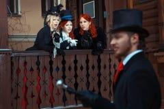 Girls discuss man in retro suit. Royalty Free Stock Image