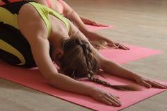 Girls do exercises tilts forward sitting on their lap Stock Photo