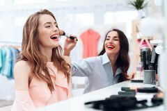 Girls do makeup in the showroom. Two beautiful girls have fun and smile. They are sitting in a bright room opposite the mirror Stock Image