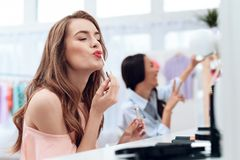 Girls do makeup in the showroom. Two beautiful girls have fun and smile. They are sitting in a bright room opposite the mirror Royalty Free Stock Photo