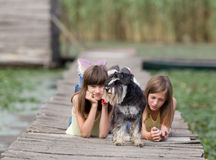 Girls with dog on dock Stock Images