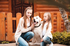 Girls with dog outdoors. Two girls sitting with labrador pet outdoors. Togetherness. Friendship Royalty Free Stock Images