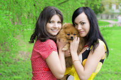 Girls with a dog in the park royalty free stock photography