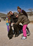 Girls and dogs. Mother and girls (best friends) with two black pariah dogs in the countryside. Vertical color photo Royalty Free Stock Image
