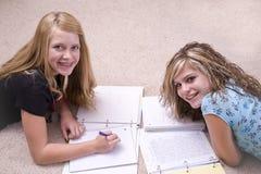 Girls doing homework. Two teenage girls laying on the ground doing homework Stock Images