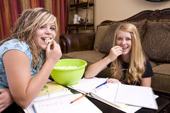 Girls doing homework while eating popcorn. Two teenager girls eating their popcorn while doing their homework Stock Photography