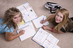 Girls doing homework looking up. Two girls doing homework with paper and pencils looking up Royalty Free Stock Photo